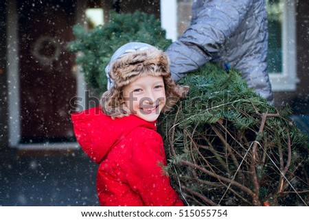 family of two bringing christmas tree home together at snowy weather, holiday concept