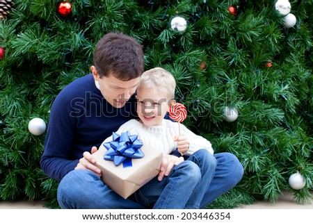 family of two enjoying christmas time by the tree with presents - stock photo
