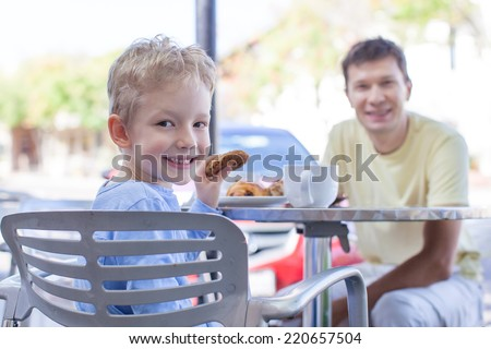 family of two enjoying desserts at outside cafe - stock photo