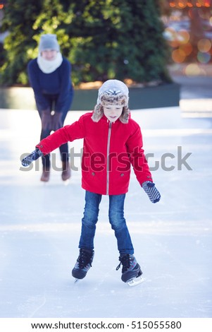 family of two enjoying ice skating at winter at outdoor skating rink decorated for holiday time at snowy weather, winter and family concept