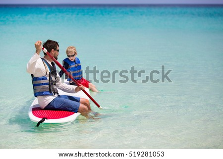 family of two enjoying stand up paddleboarding at caribbean vacation, active and healthy lifestyle