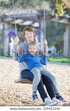 family of two enjoying time together swinging at the park - stock photo
