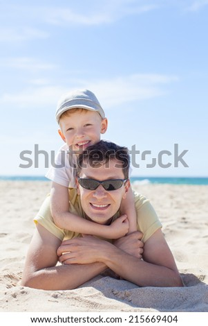family of two having fun at the beach - stock photo