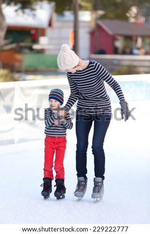 family of two having fun ice skating together at winter