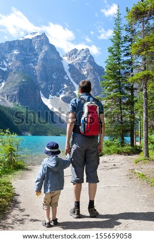 family of two hiking by lake moraine in banff national park, alberta, canada - stock photo