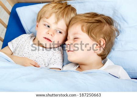 Family of two little boys: Siblings having fun in bed at home, indoors.
