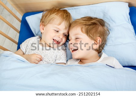 Family of two little boys: Twins having fun in bed at home, indoors.