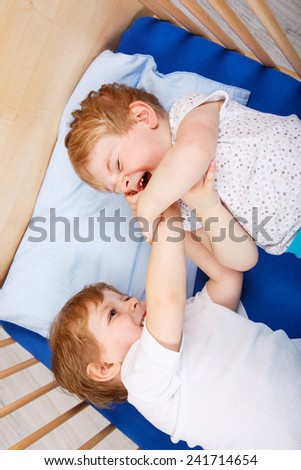 Family of two little boys: Twins having fun, playing and fighting in bed at home, indoors. - stock photo