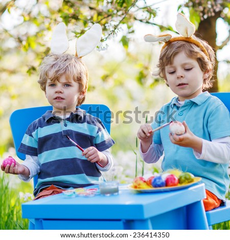 Family of two siblings: Cute twin boys wearing Easter bunny ears, painting colorful eggs and having fun outdoors. Traditional egg hunt. - stock photo
