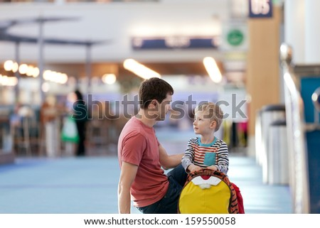 family of two waiting at the airport - stock photo