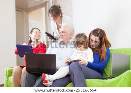 family of with portable computers on sofa   - stock photo