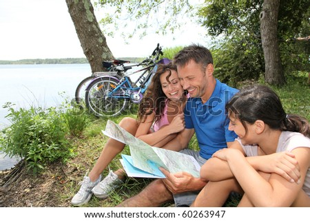 Family on a bicycle ride looking at map - stock photo