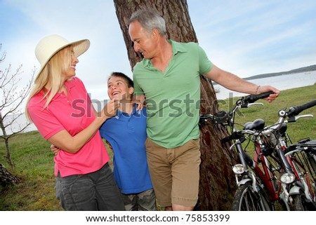 Family on a bike ride standing by a lake - stock photo
