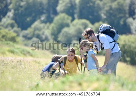 Family on a hiking day looking at vegetation
