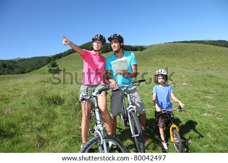 Family on a mountain bike ride in summer - stock photo