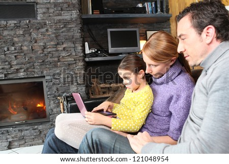 Family on a sofa in front of the fireplace - stock photo