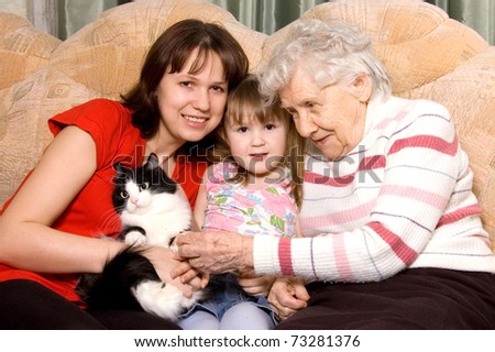 Family on a sofa with a cat - stock photo