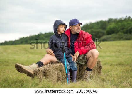 Family on a trekking day. Father and son relaxing after a forest and plain trail, focus on father - stock photo
