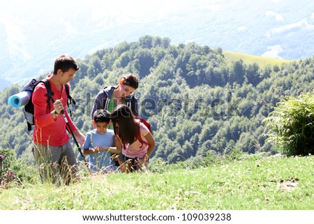 Family on a trekking day looking at wild flowers - stock photo