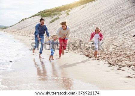 Family On Beach Vacation Running By Sea - stock photo
