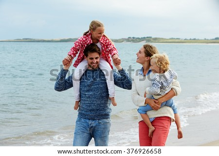 Family On Beach Vacation Walking By Sea - stock photo