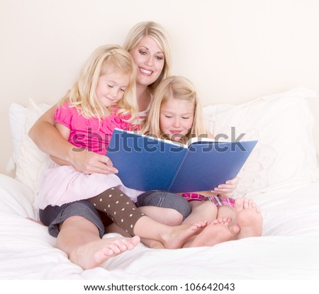 Family on bed reading book, mother and two daughters.