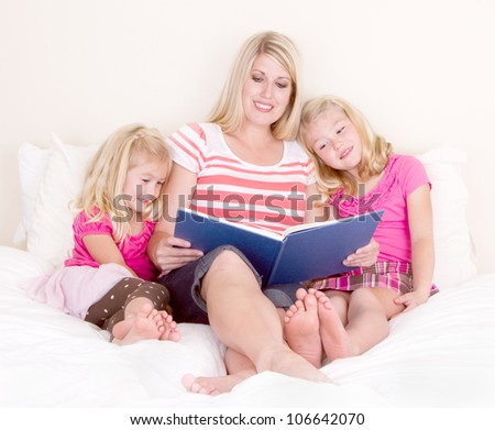 Family on bed reading book, mother and two daughters. - stock photo