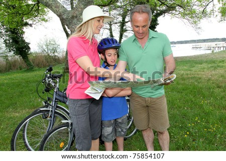 Family on bicycle ride looking at map