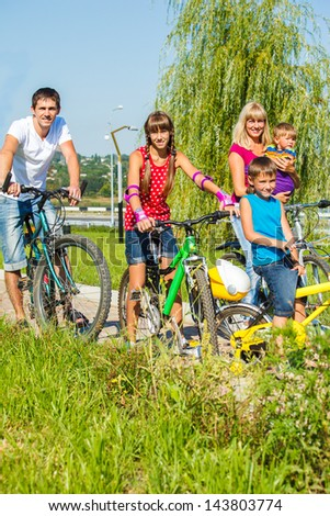 Family on bikes in a summer park - stock photo