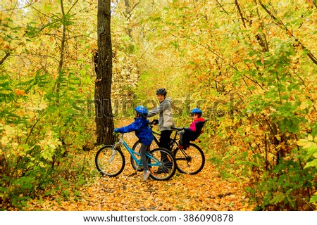 Family on bikes in autumn park, father and kids cycling, active family sport outdoors  - stock photo
