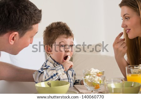 Family on breakfast - eating healthy fruit salad and having fun - stock photo