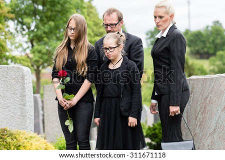 Family on cemetery or graveyard mourning deceased relative - stock photo