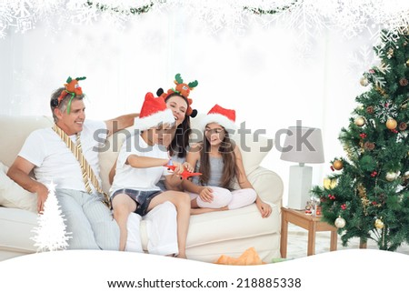 Family on Christmas day looking at their presents at home against fir tree forest and snowflakes - stock photo