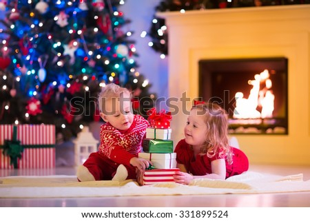 Family on Christmas eve at fireplace. Kids opening Xmas presents. Children under Christmas tree with gift boxes. Decorated living room with traditional fire place. Cozy warm winter evening at home. - stock photo