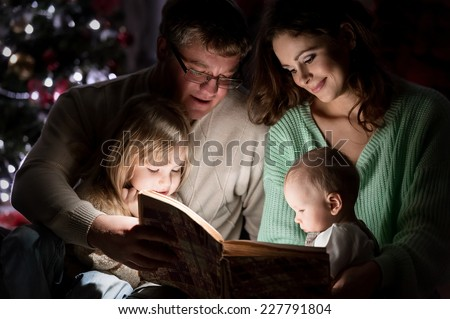 Family on Christmas Eve under the Christmas tree by the fireplace reading a book to their children with tales