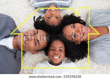 Family on floor with heads together against house outline - stock photo
