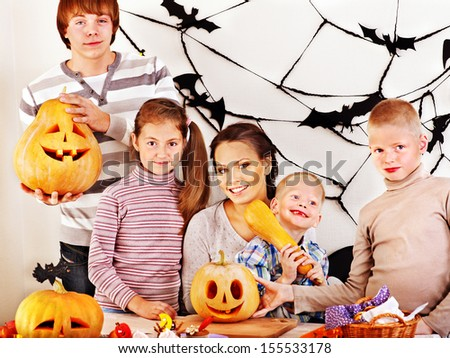 Family on Halloween party with children making carved pumpkin.