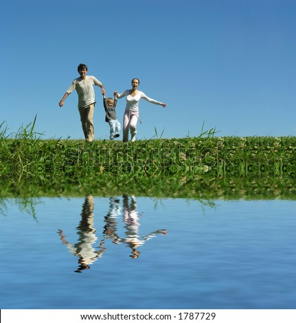 family on herb under blue sky and water - stock photo