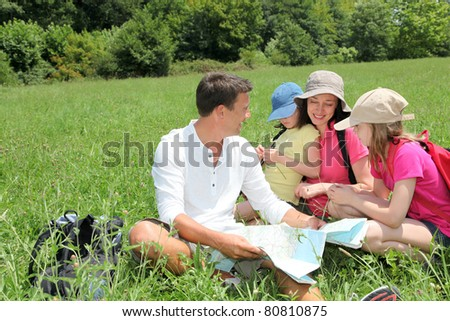 Family on hiking day looking at map - stock photo