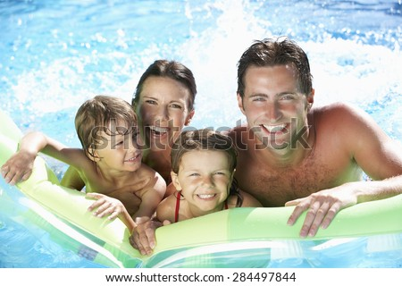 Family On Holiday In Swimming Pool - stock photo
