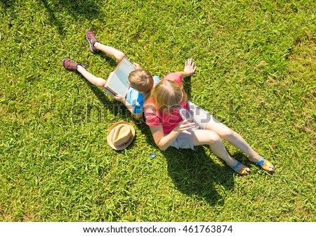 Family on nature: mother drinking water, son read book. Overhead view.