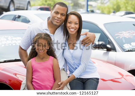Family on new car lot looking to camera - stock photo