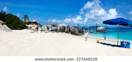 Family on picture perfect beach with blue umbrella, white sand, turquoise ocean water and blue sky at tropical island in Caribbean - stock photo