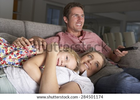 Family On Sofa Watching TV - stock photo