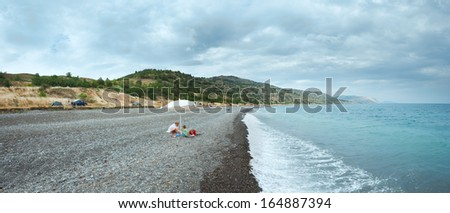 Family on summer beach in Crimea, Ukraine. Black See cloudy panorama.