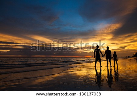 Family on the beach at sunset - stock photo