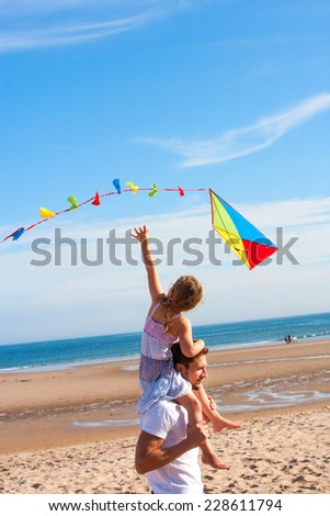 Family on the Beach Flying a Kite - stock photo