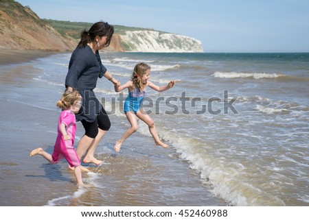 Family on the beach/ running into the sea