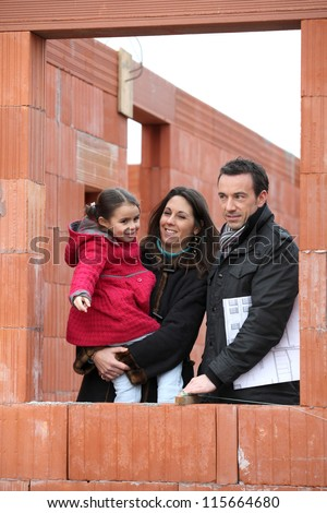 Family on the building site of their new home - stock photo
