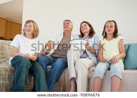 Family on the couch watching tv together - stock photo